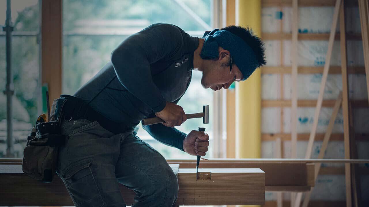 専属の大工職人が木材に鑿を入れるシーン