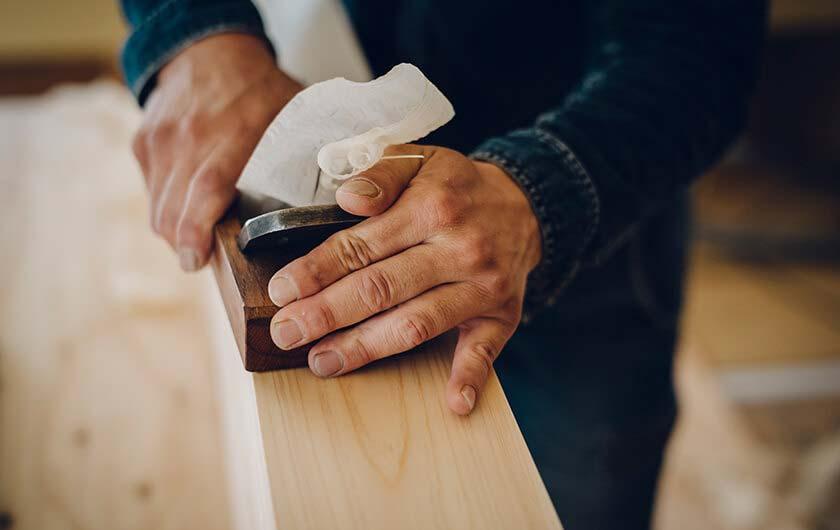 銘木の表面を鉋で削る匠。